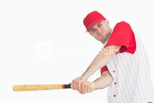 Portrait of young baseball player swinging bat