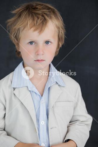 Boy dressed as teacher stands in front of black board