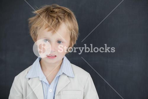 Boy dressed as teacher and stands in front of black board