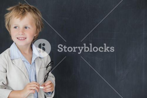 Boy dressed as teacher standing in front of black board