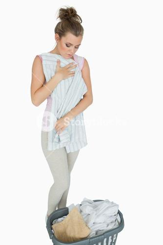Young woman folding shirt with laundry basket
