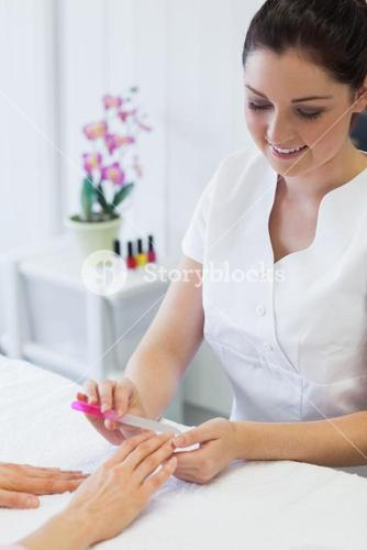 Manicurist filing womans nails