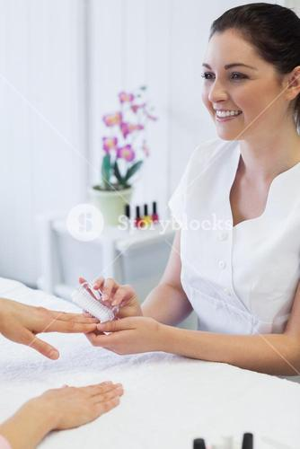 manicurist using nail brush on womans nails