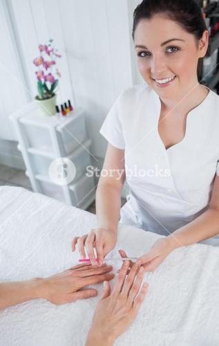 Portrait of manicurist filing womans nails