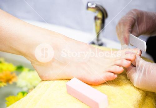 Closeup of nail technician filing womans toe nails