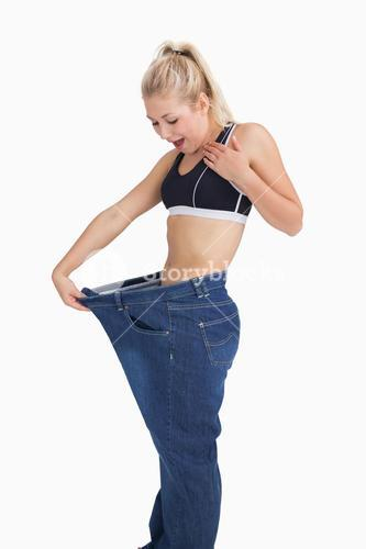 Young thin woman wearing old pants after losing weight