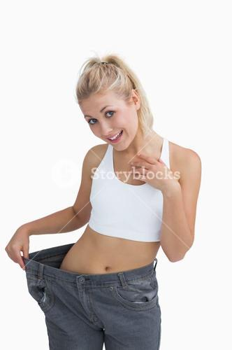 Young healthy woman wearing old pants after losing weight