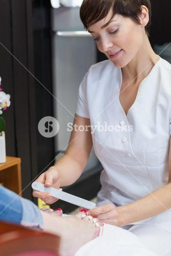 Nail technician filing womans toe nails at nail salon