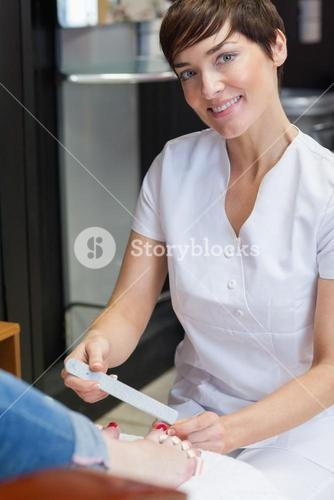 Portrait of nail technician filing womans toe nails