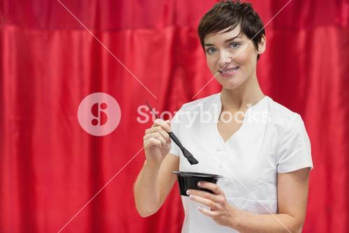 Young woman mixing hair color over red backdrop