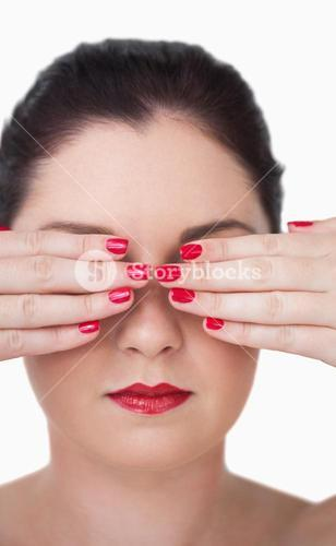 Sensuous young woman covering eyes with red painted finger nails