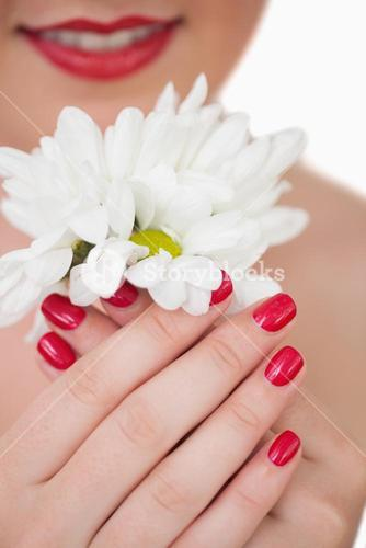 Closeup of woman with red lips and red painted nails holding flowers
