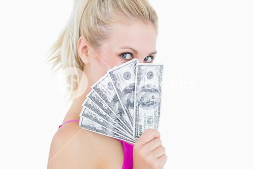 Woman holding fanned banknotes in front of face