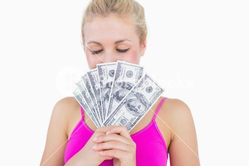 Woman holding fanned banknotes in front of face with eyes closed