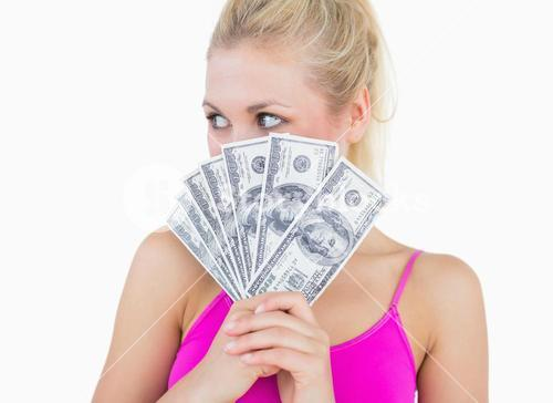Woman with fanned us banknotes looking away