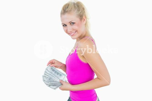 Young casual woman with fanned us banknotes