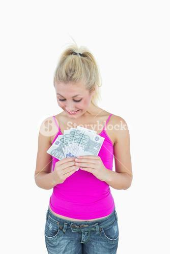 Happy young woman looking at fanned euro banknotes