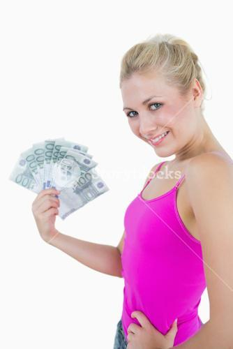 Young woman holding out fanned 100 euro banknotes
