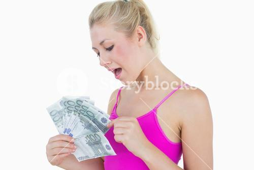 Young casual woman counting euro banknotes