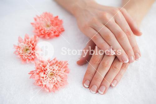 Flowers with french manicured fingers at spa center
