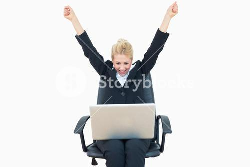 Successful business woman raising hands in victory with laptop