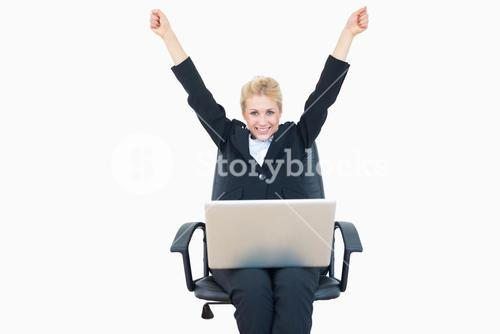 Successful business woman raising hands with laptop