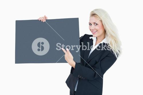 Portrait of business woman pointing at empty banner