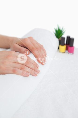 French manicured fingers and nail paint bottles