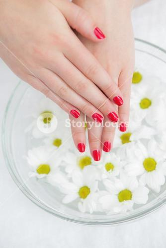 Red painted finger nails and bowl of flowers