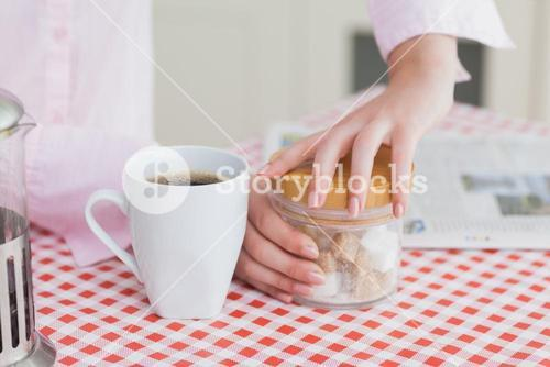 Woman with coffee cup and container of sugar cubes