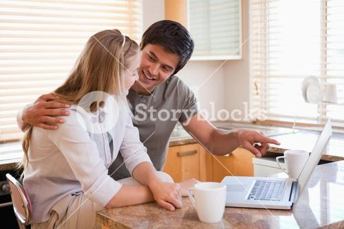 Couple using laptop together at home