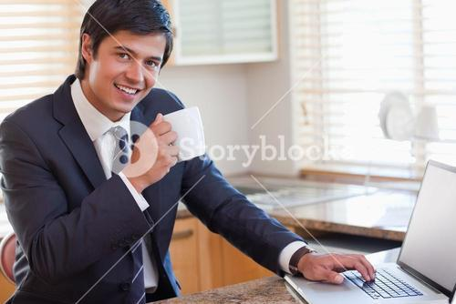 Business man using laptop and drinking coffee