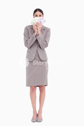 Business woman holding fanned banknotes in front of face