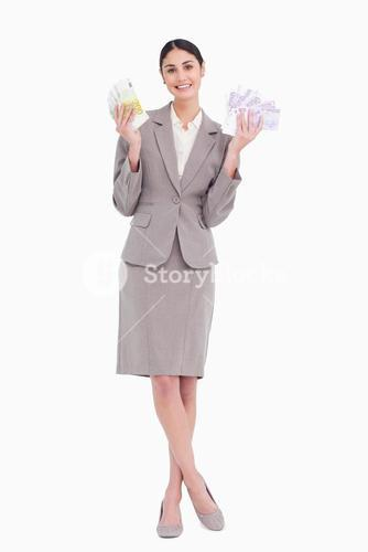 Happy business woman holding fanned banknotes