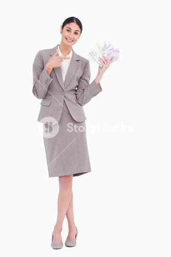 Portrait of happy business woman pointing at banknotes