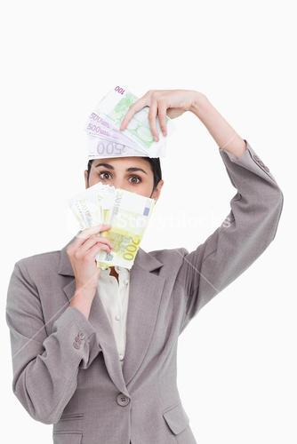 Business woman holding fanned banknotes over face