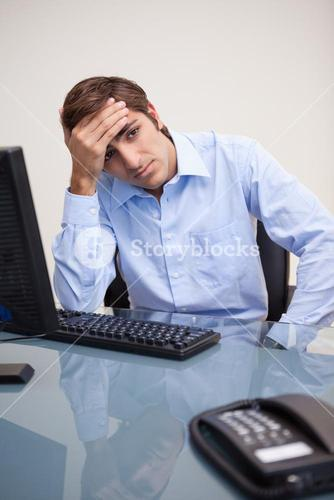 Young tense business man sitting at office desk