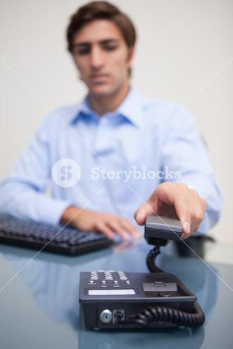 Business man using telephone at office desk