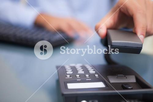 Man with telephone receiver at desk