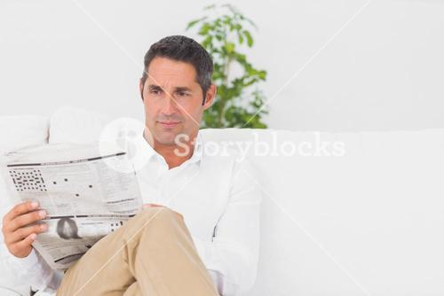 Serious man reading a news paper