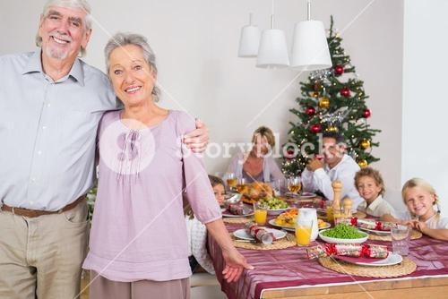 Grandparents standing by the dinner table