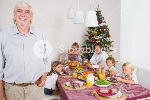 Smiling grandfather standing at the dinner table