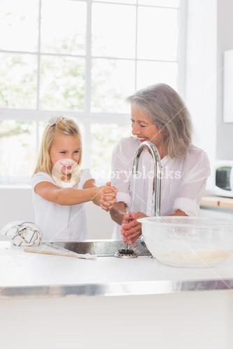 Smiling grandmother and granddaughter washing hands