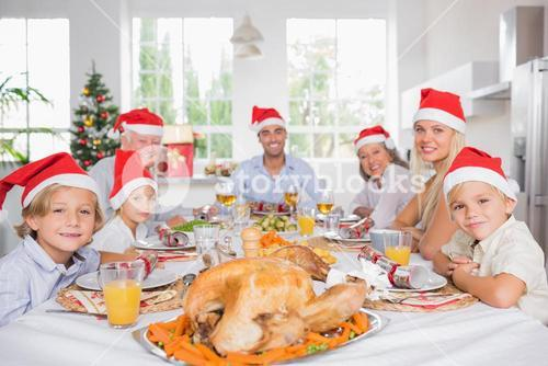 Happy family wearing santa hats around the dinner table