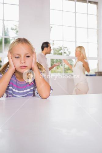 Girl looking despressed in front of fighting parents