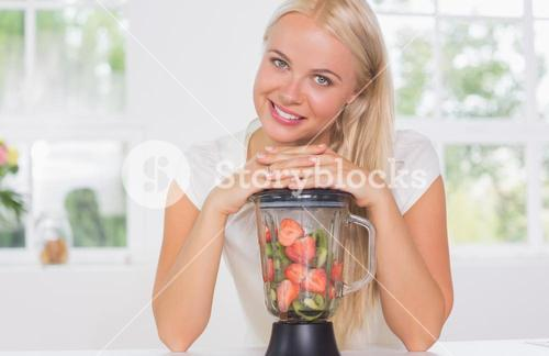 Smiling woman putting hands on the mixer
