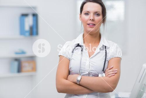 Confident female doctor with arms crossed at clinic