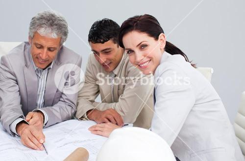 Portrait of a female engineer studying plans with her colleagues