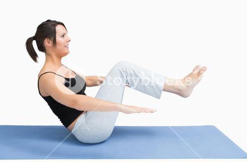 Side view of young woman exercising on yoga mat