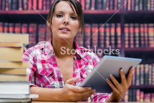 College student with digital tablet and stack of books at library